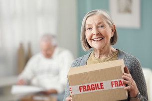 Senior woman holding parcel, portraitの写真素材 [FYI03482452]