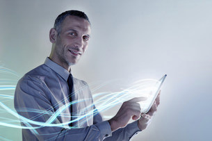 Businessman using digital tablet with lightsの写真素材 [FYI03482548]