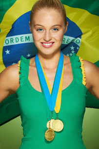Young woman in front of Brazilian flag with medalsの写真素材 [FYI03482654]