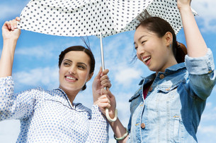Two young women outdoors with parasolの写真素材 [FYI03482688]