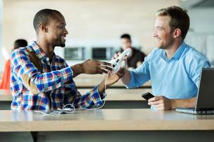 Young men sharing headphonesの写真素材 [FYI03482692]