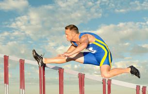 Male hurdler clearing hurdleの写真素材 [FYI03482722]