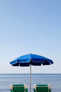 Blue parasol and sun loungers by the seaの写真素材 [FYI03482844]