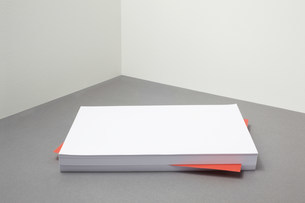 Red piece of paper amongst stack of blank paperの写真素材 [FYI03483005]