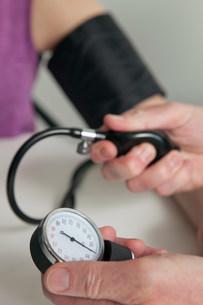 Doctor using blood pressure gauge on patient during medicalの写真素材 [FYI03483171]