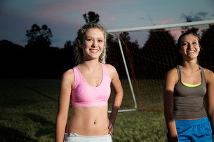 Portrait of two girls on soccer pitch at nightの写真素材 [FYI03483315]