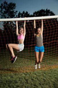 Girls hanging from soccer goalの写真素材 [FYI03483319]