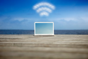 Laptop with wifi symbol at the coastの写真素材 [FYI03483416]