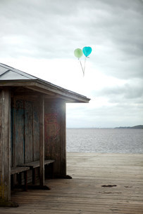 Balloons floating by old seaside shelter, Flensburg, Germanyの写真素材 [FYI03483417]