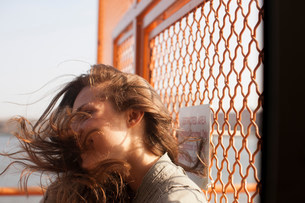 Young woman on a ferry, wind blowing hairの写真素材 [FYI03483477]
