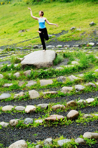 Woman in yoga pose on stone in mazeの写真素材 [FYI03483504]