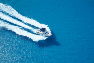 Motor yacht ploughing across blue seaの写真素材 [FYI03483510]