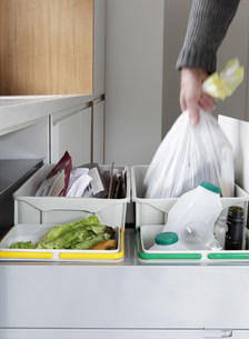 Person removing rubbish bag from waste and recycling drawerの写真素材 [FYI03483589]