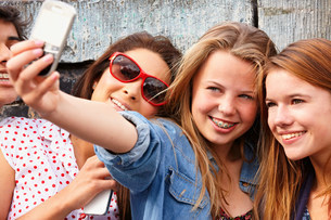 Teenage girls taking a picture of themselves on smartphoneの写真素材 [FYI03483617]