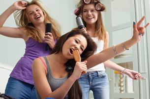 Teenage girls singing into hairbrushesの写真素材 [FYI03483637]
