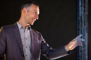 Businessman touching virtual informationの写真素材 [FYI03483758]