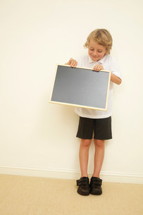Schoolboy holding blank blackboardの写真素材 [FYI03483825]