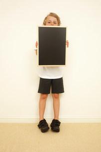 Schoolboy holding blank blackboardの写真素材 [FYI03483826]