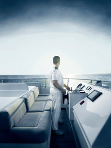 Captain at helm of large motor yachtの写真素材 [FYI03483844]