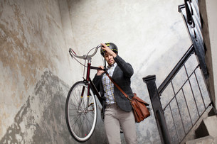 Man carrying bicycle down staircaseの写真素材 [FYI03483994]