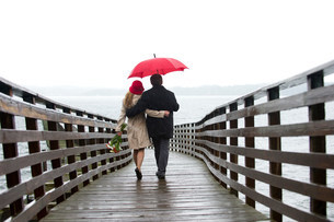 Couple walking on wooden pier in rainの写真素材 [FYI03484085]