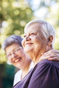 Older women smiling together outdoorsの写真素材 [FYI03484111]