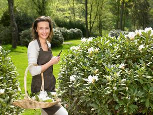 Woman gardening outdoors smilingの写真素材 [FYI03484702]