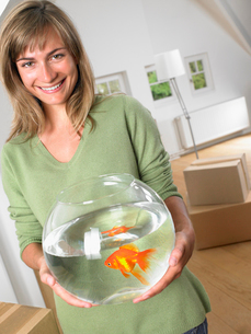 Woman holding fishbowl in new home smilingの写真素材 [FYI03484726]