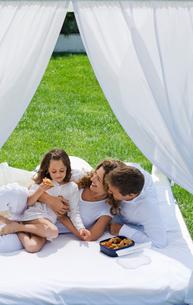 Family having breakfast on bed in gardenの写真素材 [FYI03484984]