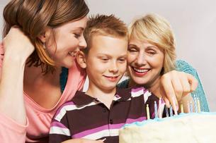 Grandmother,boy and mom decorating cakeの写真素材 [FYI03485285]