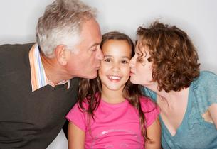 Grandpa and Mum kissing girl's cheekの写真素材 [FYI03485292]