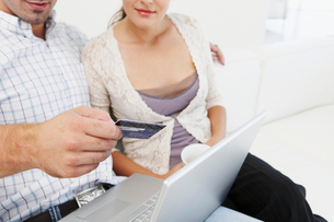 Couple on sofa,making purchase onlineの写真素材 [FYI03485566]