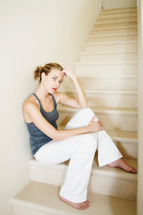 Serious woman sits on staircaseの写真素材 [FYI03485586]