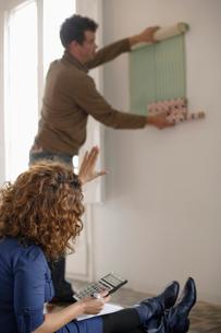 Couple Trying Wallpaperの写真素材 [FYI03486111]