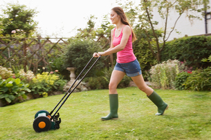 Woman mowing lawn with grass mowerの写真素材 [FYI03486285]