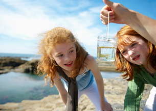 2 girls looking at fish in jar by seaの写真素材 [FYI03486351]