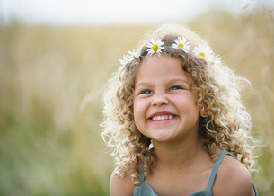 Young girl laughing with daisies in hairの写真素材 [FYI03486356]