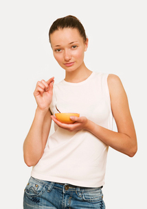 Girl eating a pink grapefruitの写真素材 [FYI03486408]