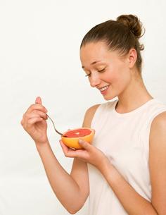 Girl eating a pink grapefruitの写真素材 [FYI03486427]