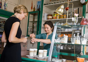 Female barista helping a female customerの写真素材 [FYI03486501]