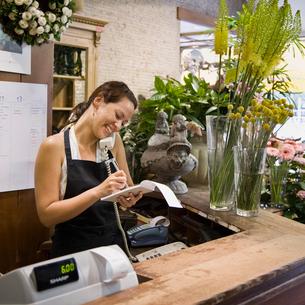 Female clerk in a flower shopの写真素材 [FYI03486518]
