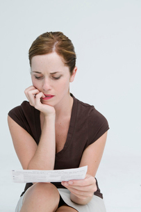 A worried woman looking at a bill.の写真素材 [FYI03486596]