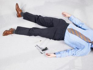 Man lying on floor with gunの写真素材 [FYI03486786]