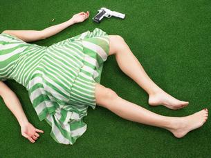 Woman lying on floor with gunの写真素材 [FYI03486795]