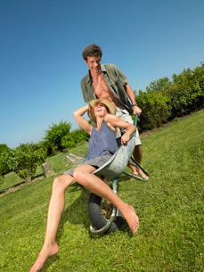 Man pushing woman in a wheelbarrowの写真素材 [FYI03486986]