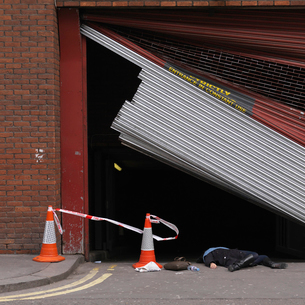 Woman lying underneath broken shutterの写真素材 [FYI03487149]