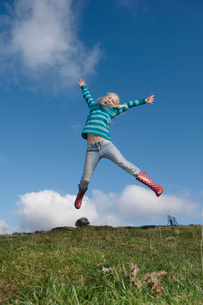 Girl jumping on hillの写真素材 [FYI03487180]