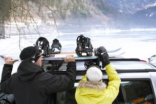 Couple taking snowboards of roof rackの写真素材 [FYI03487648]