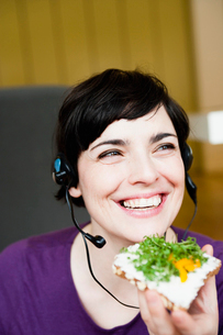 Woman in office having a snackの写真素材 [FYI03487694]