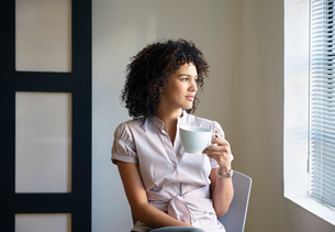 Young woman with cup,thinkingの写真素材 [FYI03487814]
